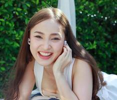 retrato bela jovem asiática com sorriso limpo encantador, lindas garotas relaxam ouvindo música em casa nas férias. foto