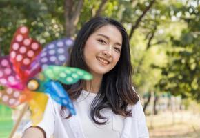 linda mulher asiática brincando com turbinas no parque alegremente. conceito de viver um feriado feliz foto
