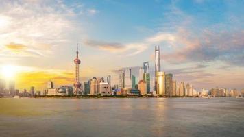 lado de pudong do horizonte da cidade de Xangai olhando através do rio huangpu em um dia ensolarado foto