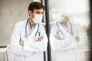 médico usando uma máscara com reflexo em uma janela foto