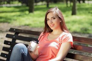 mulher relaxando em um banco do parque foto
