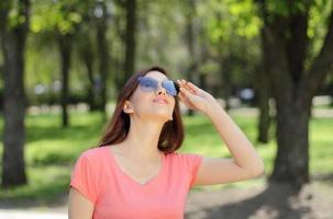 mulher usando óculos escuros enquanto está em um parque foto