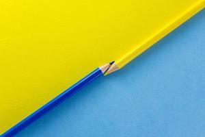 lápis de cor em papéis de cor amarela e azul dispostos diagonalmente foto