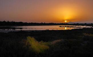 pôr do sol no lago salgado de Larnaca sem o pôr do sol e as turbinas eólicas à distância foto
