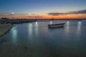 pôr do sol em la paz baja california sur mexico com um barco no mar e o reflexo das luzes na água perto da praia foto