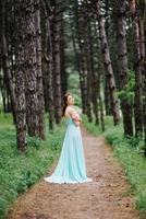 garota feliz em um vestido longo turquesa em um parque verde foto