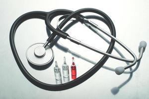 um estetoscópio tradicional e três tubos de vacinação foto