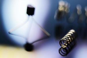 imagem macro de uma mola de metal e componentes eletrônicos borrados foto
