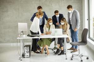 profissionais mascarados olhando para um computador foto