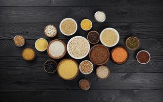 cereais, grãos, sementes e sêmolas, fundo preto de madeira foto