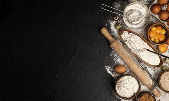 Assar ingredientes na vista superior do fundo preto foto