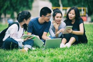 grupo de estudantes asiáticos no gramado do campus foto