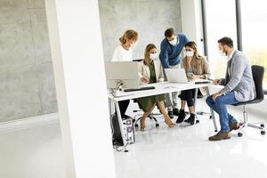 grupo de empresários em uma reunião usando máscaras foto