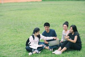 grupo de alunos sentados na grama foto