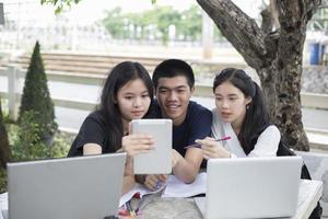 três estudantes asiáticos usando um tablet para estudar foto