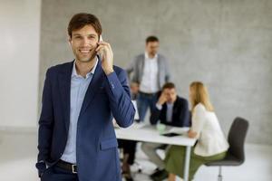 homem no telefone com a equipe em segundo plano foto