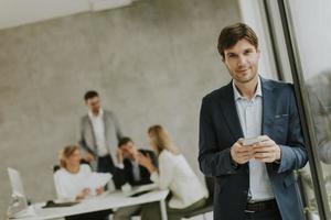 homem enviando mensagens de texto com a equipe no fundo foto