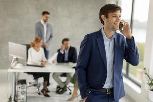 homem falando ao telefone com a equipe em segundo plano foto