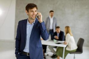 homem no telefone enquanto a equipe está em uma reunião foto