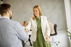 dois profissionais apertando as mãos em um escritório foto