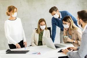 reunião de negócios com profissionais mascarados foto