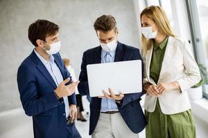 três profissionais mascarados com laptop foto