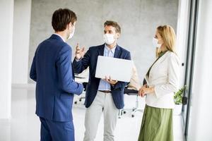 três profissionais mascarados discutindo com o laptop foto