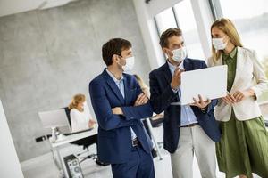 três profissionais mascarados em uma reunião foto