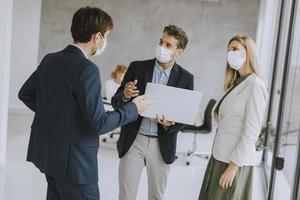 três profissionais mascarados em pé e conversando com o laptop foto