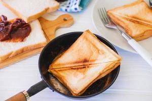 pão torrado assado saindo de uma torradeira de aço inoxidável em uma cozinha doméstica. foto