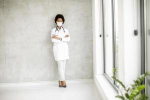 médico encostado em uma parede cinza foto