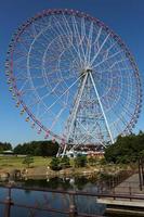 roda-gigante no parque de diversões com céu azul foto