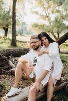 jovem casal apaixonado um cara com barba e uma garota com cabelos escuros em roupas leves foto