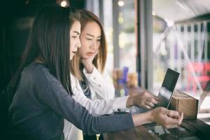 duas mulheres de negócios asiáticas trabalhando em um laptop foto
