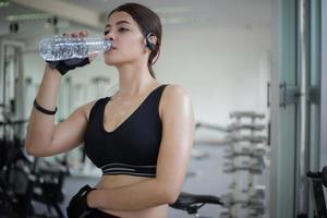 mulher bebendo água durante um treino foto