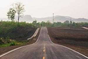 uma longa estrada reta levando a uma montanha foto