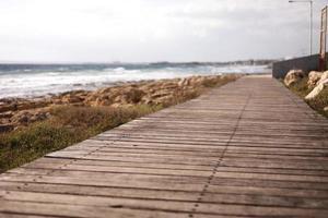 bela passarela de pedestres de madeira à beira-mar foto
