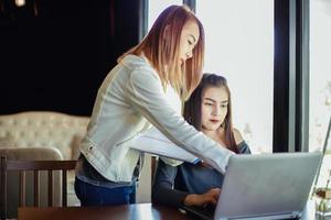 duas mulheres de negócios asiáticas usando um laptop foto
