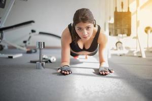 mulher em pose de prancha no ginásio foto