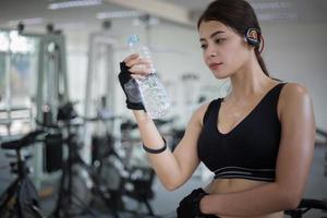 mulher bebendo água no ginásio foto