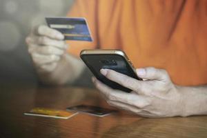 compras de pagamento on-line com o homem de cartão de crédito usando o conceito de e-commerce e aplicativo de negócios de smartphone móvel foto