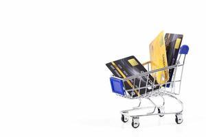 cartões de crédito em um carrinho de compras isolado no fundo branco conceito de pagamento on-line de compras de negócios foto