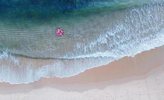 vista aérea superior do drone vista do menino com anel de natação no mar e sombra de água azul esmeralda e espuma de ondas ao nascer do sol foto
