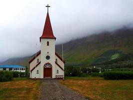 igreja islandesa e névoa baixa nos fiordes ocidentais da Islândia foto