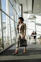 empresária andando e falando no telefone enquanto segura uma pasta foto