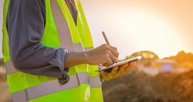 faixa do homem com colete de segurança escrevendo no tablet digital foto