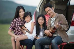 família sentada do lado de fora do carro tocando cavaquinho foto