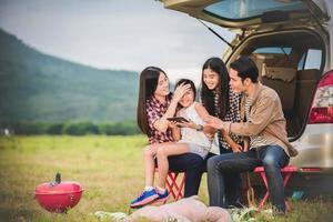 família acampando fora do carro na viagem foto