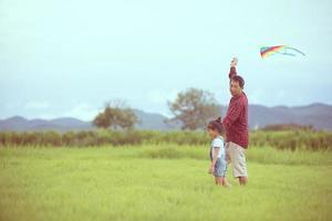 filho e pai brincando com pipa no parque foto