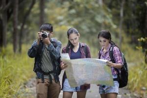 grupo de jovens amigos caminhando na floresta foto